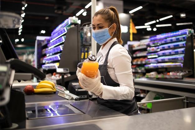 Kassiererin im supermarkt mit maske und handschuhen, die vollständig gegen das koronavirus geschützt sind Kostenlose Fotos