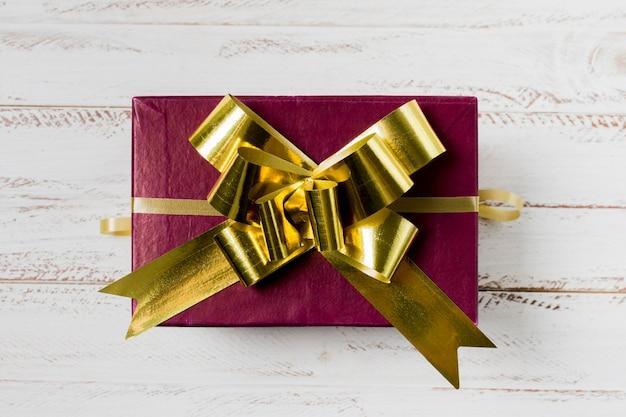 Kastanienbraune geschenkbox mit goldenem band über hölzernem schreibtisch Kostenlose Fotos