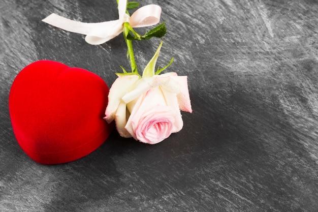 Kasten mit einem ring und einer rosarose auf einem dunklen hintergrund. kopieren sie platz Premium Fotos