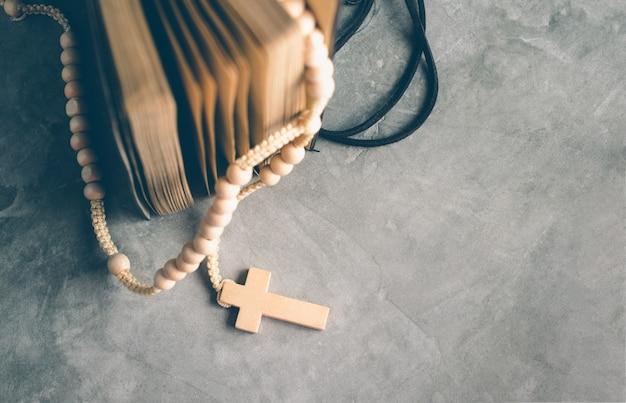Katholische rosenkranzperlen mit altem buch auf zementtabellengebet, rosenbeethintergrundkonzept im weinleseton. Premium Fotos
