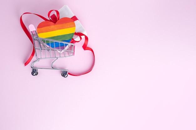 Kauf eines lgbt-geschenks für das valentinstagskonzept. geschenkbox mit rotem band und gemalter papier-lgbt-herzform im einkaufswagen auf rosa hintergrund Premium Fotos