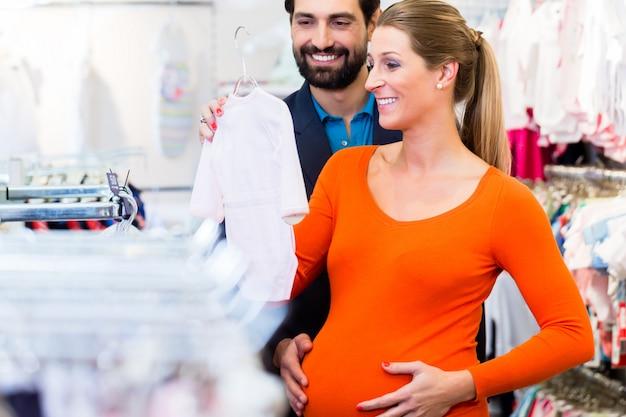 Kaufende babykleidung der schwangeren frau und des mannes im speicher Premium Fotos