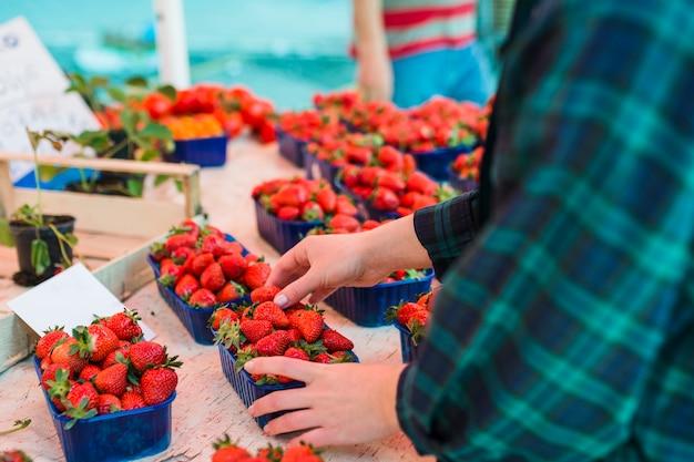 Kaufende erdbeeren der person am supermarkt Kostenlose Fotos