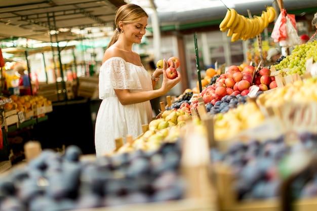 Kaufende früchte der jungen frau auf dem markt Premium Fotos
