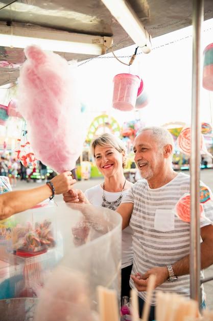 Kaufende zuckerwatte des glücklichen paars des hohen winkels Kostenlose Fotos