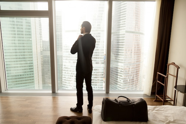 Kaufmann genießt blick vom fenster im hotelzimmer Kostenlose Fotos