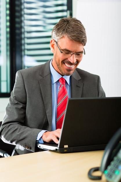 Kaufmann mit laptop in seinem büro Premium Fotos