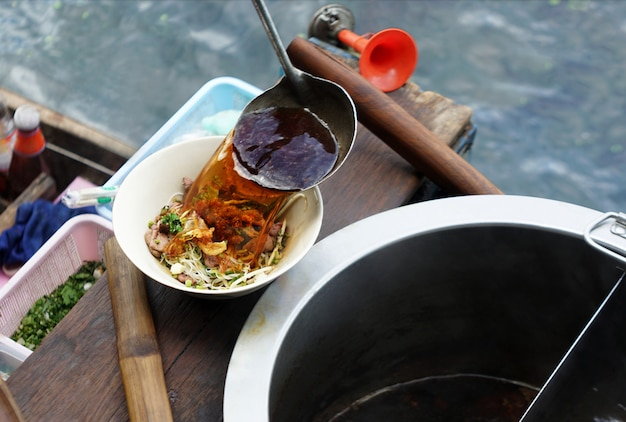 Kaufmannskoch, der kräuterhitzesuppe in weiße schüssel thailändische art der nudel auf dem schwimmen des hölzernen bootes im fluss gießt. Premium Fotos