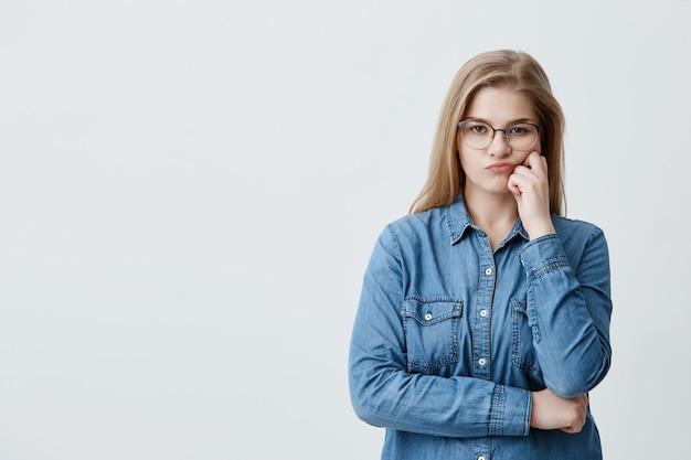 Kaukasische blonde hübsche frau im jeanshemd mit brille, die ihre lippen in unzufriedenheit schmollt, während sie zweifelt. nachdenkliches mädchen, das arme verschränkt, sieht mit enttäuschung und beleidigung aus Kostenlose Fotos