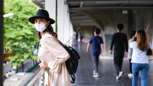 Kaukasische frau, die auf u-bahn-kreuzung in der medizinischen gesichtsmaske während der pandämie in der stadt bangkok geht. Kostenlose Fotos