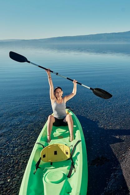 Kaukasische frau, die in einem grünen kajak sitzt und die paddel zum himmel erhebt. Premium Fotos