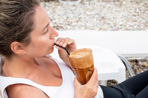 Kaukasische frau, die kaffeegetränk an einem strand mit schaum und trinkhalm trinkt Kostenlose Fotos