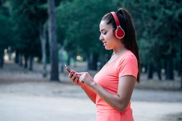 Kaukasische frau, die musik in einem park hört Premium Fotos