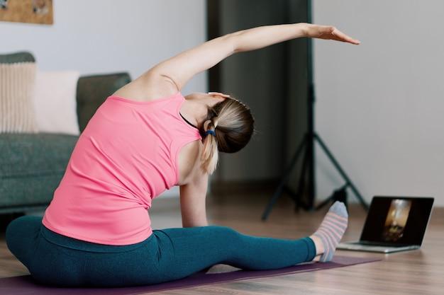 Kaukasische frau, die yoga zu hause praktiziert Kostenlose Fotos