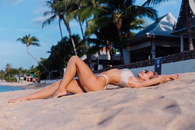 Kaukasische frau im bikini und in der sonnenbrille am tropischen strand Kostenlose Fotos