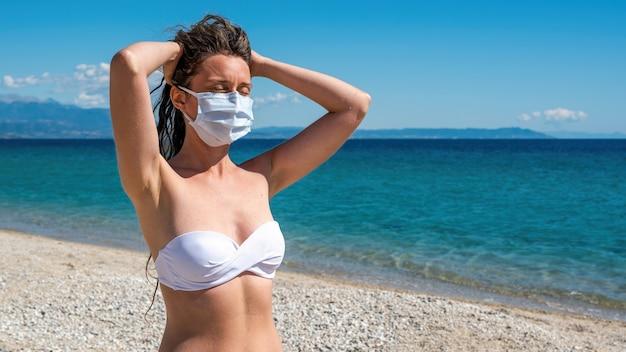 Kaukasische frau in der weißen medizinischen maske mit den erhobenen händen zum kopf und den geschlossenen augen im badeanzug an einem strand in asprovalta, griechenland Kostenlose Fotos
