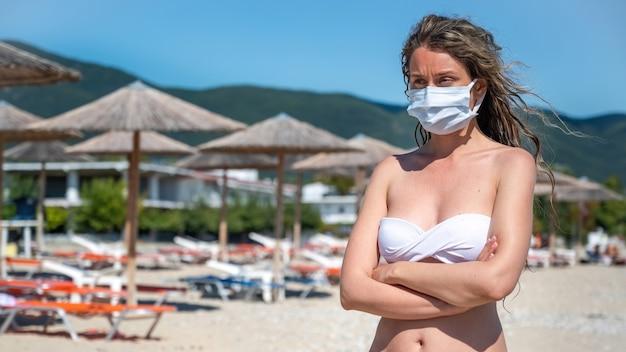 Kaukasische frau in der weißen medizinischen maske mit gekreuzten händen im badeanzug an einem strand in asprovalta, griechenland Kostenlose Fotos