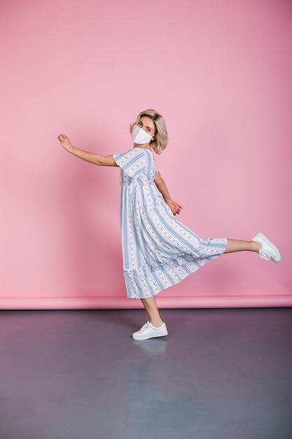 Kaukasische frau mit blondem haar und maske gestikuliert einen lauf, der ein kleid auf einer rosa wand trägt Premium Fotos