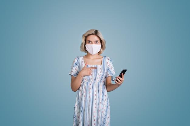 Kaukasische frau mit blonden haaren und maske, die ein kleid trägt, zeigt erstaunt auf ihr telefon auf einer blauen studiowand Premium Fotos