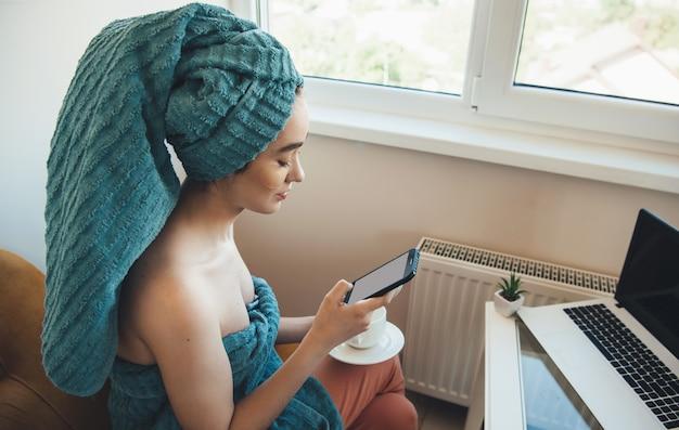 Kaukasische frau mit einem handtuch auf dem kopf plaudert auf handy und laptop zu hause nach dem bad Premium Fotos