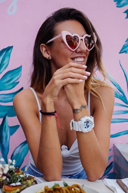 Kaukasische glückliche frau, die gesundes frühstück im café auf hintergrund der rosa tropischen wand hat. herz trendige sonnenbrille. Kostenlose Fotos
