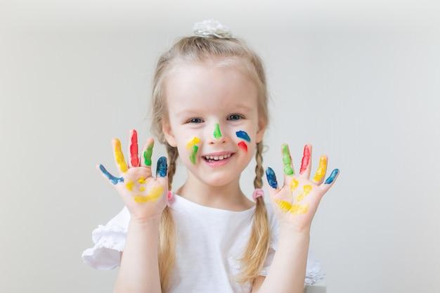 Kaukasische kleines mädchen-malerei mit den bunten handfarben zu hause die früherziehung, die für schulvorschulentwicklungs-kinderspiel sich vorbereitet Premium Fotos