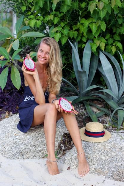 Kaukasische ruhige glückliche frau im blauen kleid hält drachenfrucht am tropischen strand Kostenlose Fotos