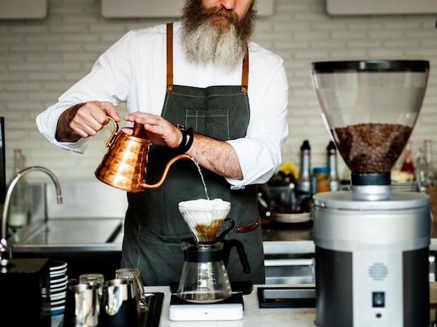 Kaukasischer baristamann, der tropfenfängerkaffee bildet Kostenlose Fotos