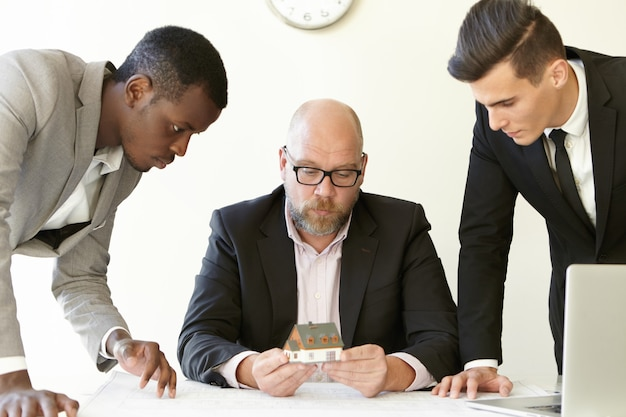 Kaukasischer chef in gläsern, die modellhaus der zukünftigen immobilien halten, während zwei junge architekten ihm bauprojekt präsentieren. Kostenlose Fotos