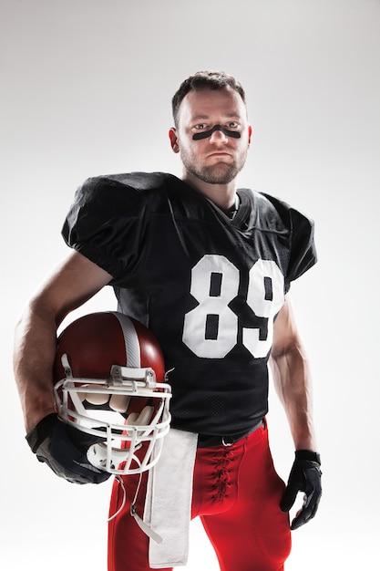 Kaukasischer fitnessmann als amerikanischer fußballspieler auf weißem hintergrund Kostenlose Fotos