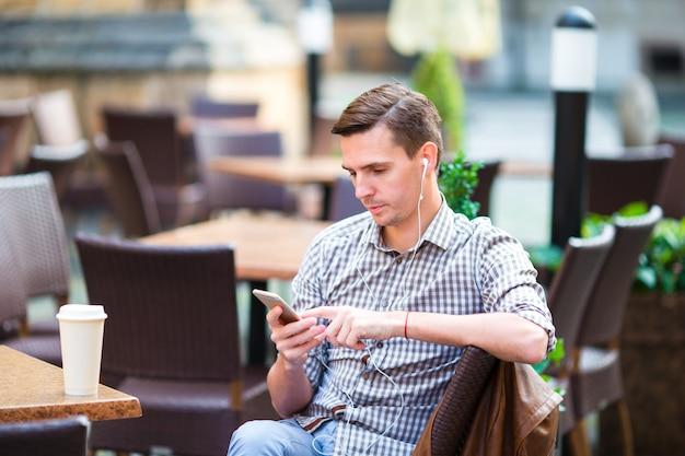 Kaukasischer junge hält mobiltelefon draußen auf der straße. mann mit mobilen smartphone. Premium Fotos