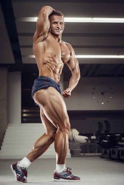 Kaukasischer kraftsportler, der beinquadrizepsmuskeln aufpumpt. starker bodybuilder mit sixpack, perfekter bauchmuskulatur, trizeps, brust, schultern im fitnessstudio. fitness- und bodybuilding-konzept Premium Fotos