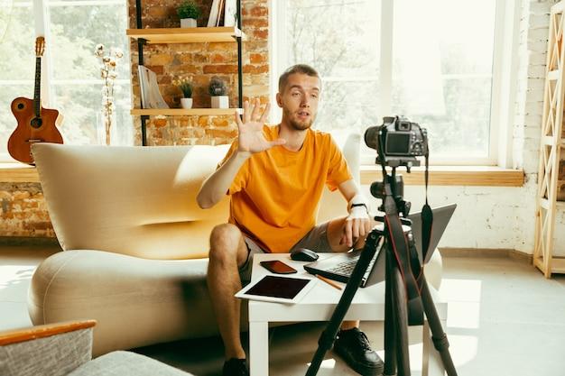 Kaukasischer männlicher blogger mit kameraaufzeichnung videoüberprüfung von gadgets zu hause Kostenlose Fotos