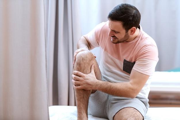 Kaukasischer männlicher patient, der auf krankenhausbett sitzt und knie hält, das er verletzt. Premium Fotos