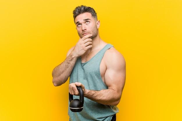 Kaukasischer mann, der den hantel seitlich schaut mit zweifelhaftem und skeptischem ausdruck hält. Premium Fotos
