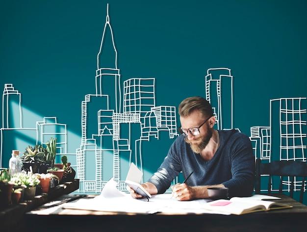 Kaukasischer mann, der mit gebäudeillustration auf grünem hintergrund arbeitet Kostenlose Fotos