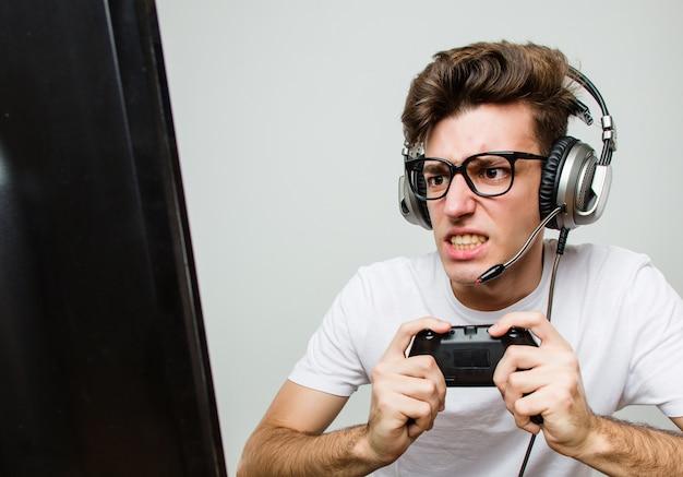 Kaukasischer mann des jugendlichen, der computerspiele spielt Premium Fotos