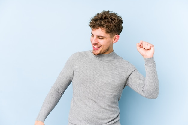 Kaukasischer mann des jungen blonden gelockten haares, der spaß tanzt und hat. Premium Fotos
