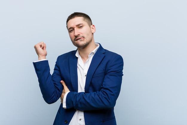 Kaukasischer mann des jungen geschäfts, der sich zurück vom kopf berührt, eine wahl denkt und trifft. Premium Fotos