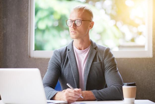 Kaukasischer mann im blazer und in gläsern, die am schreibtisch im büro sitzen, stift halten und weg schauen Kostenlose Fotos