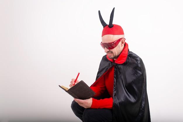 Kaukasischer mann in der roten sonnenbrille und im halloween-kostüm mit stift und notizbuch über weißem studiohintergrund. Premium Fotos