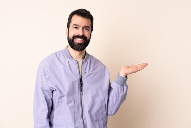 Kaukasischer mann mit bart, der eine jacke über isoliertem raum hält, der imaginären copyspace auf der handfläche hält, um eine anzeige einzufügen Premium Fotos