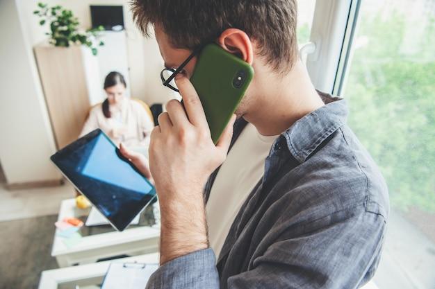 Kaukasischer mann mit brille schaut auf den tablettbildschirm, während er am telefon spricht Premium Fotos