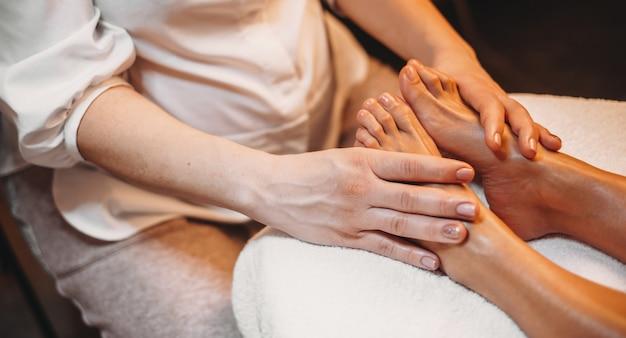 Kaukasischer masseur, der eine beinmassage mit dem auf der couch liegenden klienten hat Premium Fotos