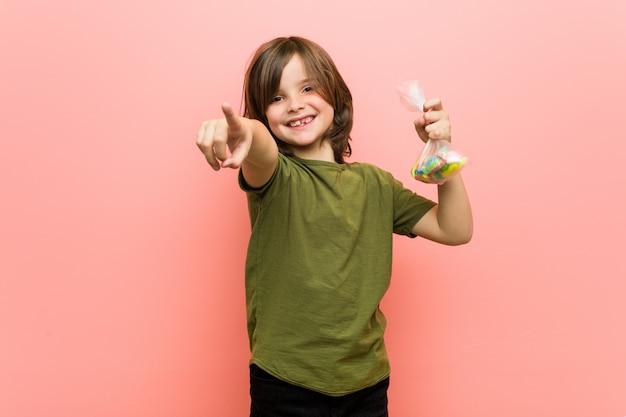 Kaukasisches haltenes freundliches lächeln der süßigkeiten des kleinen jungen, das auf front zeigt. Premium Fotos