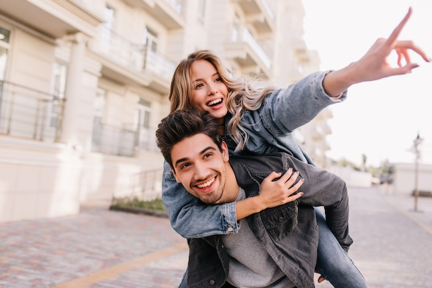 Kaukasisches hübsches mädchen, das mit freund durch stadt geht. lächelnder brünetter mann, der wochenende mit freundin verbringt. Kostenlose Fotos