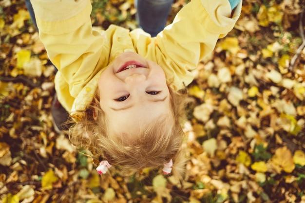 Kaukasisches kindermädchen gekleidet in einer jacke, die in die kamera lächelt. Premium Fotos