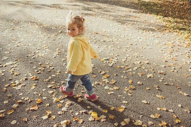 Kaukasisches kindermädchen gekleidet in einer jacke geht in den parkherbst. Premium Fotos