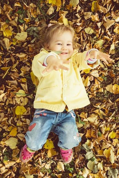 Kaukasisches kindermädchen in einer jacke liegt auf dem boden im herbstlaub. Premium Fotos