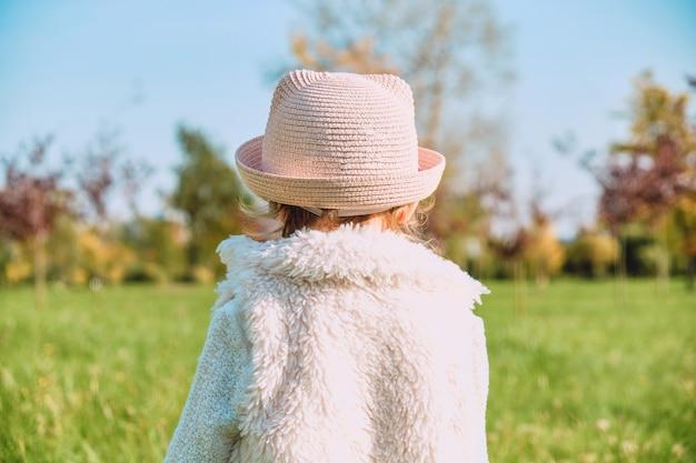Kaukasisches kindermädchen in rustikalen kleidern geht mit ihrem rücken in den herbstpark. Premium Fotos